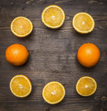 Halved oranges, lined frame  wooden rustic background top view close up Stock Photo
