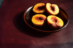 Halved peaches on dark brown plate and surface Royalty Free Stock Image