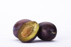Halved plum on white background_2. Halved fresh and ripe plum on white background.Composition of three Royalty Free Stock Photo