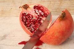 Halved pomegranate. On wooden table Royalty Free Stock Photos
