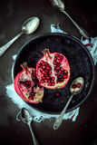 Halved pomegranate on a plate. View from above of a fresh halved pomegranate on a plate showing the juicy ripe red sweet seeds with spoons for eating on a dark royalty free stock photo