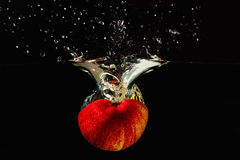 Halved red apple falling into water with splash Stock Photos