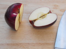 Halved red delicious apple. Red delicious apple cut in half with a chef's knife on a wooden cutting board Royalty Free Stock Image
