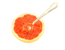 Halved red grapefruit with spoon isolated Royalty Free Stock Photos