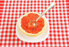 Halved red grapefruit on tablecloth Stock Images