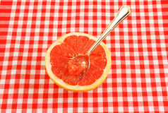 Halved red grapefruit on tablecloth Stock Photography