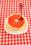 Halved red grapefruit on tablecloth Royalty Free Stock Photo