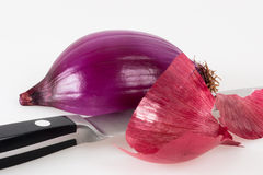 Halved red onion with a kitchen knife Royalty Free Stock Images