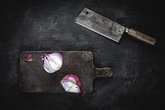 Halved Red Onion on Vintage Cutting Board with Meat Cleaver. Fresh Halved Red Onion on Vintage Brown Cutting Board with Old Meat Cleaver stock photography
