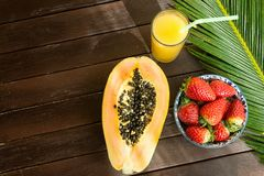 Halved Ripe Papaya Fresh Strawberries in Bowl Pineapple Juice in Tall Glass with Straw Palm Leaf on Plank Wood Table in Cafe. Vacations Summer Travel Stock Images