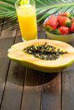 Halved Ripe Papaya Fresh Strawberries in Bowl Pineapple Juice in Tall Glass with Straw Palm Leaf on Plank Wood Table. In Cafe. Vacations Summer Travel Stock Photos