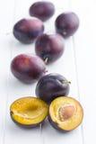 Halved ripe plum. Halved ripe plum on white table Royalty Free Stock Photo