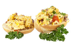 Halved roll with scrambled eggs Stock Images