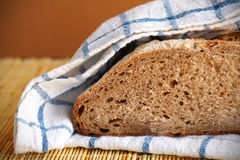 Halved rye bread loaf wrapped in the kitchen towel Stock Photo