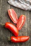 San marzano tomatoes. Halved San marzano tomatoes on old wooden table. Top view Royalty Free Stock Photos
