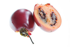 Halved Tamarillo. A tamarillo cut in half and isolated against a white background Royalty Free Stock Image