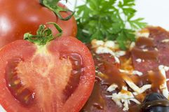 Halved tomato with slice of pizza and parsley in background Royalty Free Stock Photography