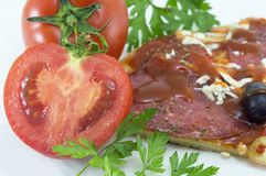 Halved tomato with slice of pizza and parsley in background Royalty Free Stock Photos