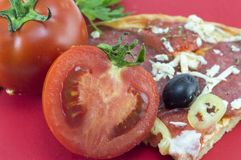 Halved tomato with slice of pizza and parsley in background Stock Photography