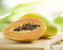 Halved and whole papaya on a wooden board Royalty Free Stock Photos