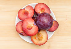 Halved And Whole Plums In Bowl On Table Stock Images