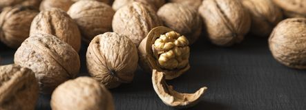 Halved and whole walnuts on black background, side view. royalty free stock photos