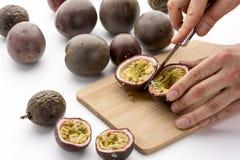 Halvera passionfrukter med en kökkniv Royaltyfri Foto
