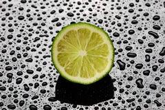 Halverad ny limefrukt på en våt svart bakgrund Arkivfoton