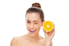 Halverad orange för kvinna holding Royaltyfri Foto