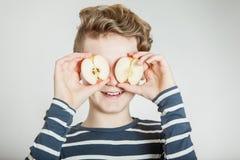 Halverar det hållande äpplet för barnet framme av hans ögon Royaltyfria Foton