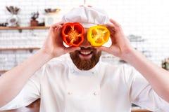 Halverar hållande spanska peppar för kock framme av hans ögon Royaltyfria Foton