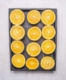 Halverar upp apelsiner i ett träslut för bästa sikt för bakgrund för svart ask trälantligt Arkivfoton