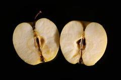 Halverat äpple på svart ställe arkivfoton