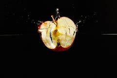 Halverat äpple som faller in i vattnet med en färgstänk fotografering för bildbyråer