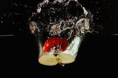 Halverat moget äpple som faller in i vatten med färgstänk royaltyfri fotografi
