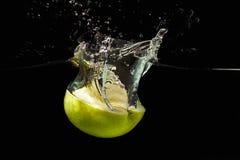 Halverat moget grönt äpple som faller in i vattnet royaltyfri bild