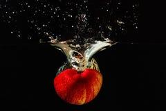 Halverat rött äpple som faller in i vatten med färgstänk arkivfoton