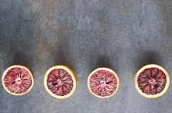 Halves of blood oranges on the grey surface.Empty space for your design. stock photography