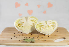 Halves of cabbage in shape of hearts. Creative food concept. Light background stock photo