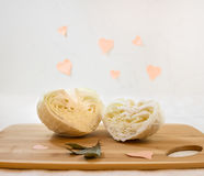 Halves of cabbage in shape of hearts. Creative food concept. Light background royalty free stock photos