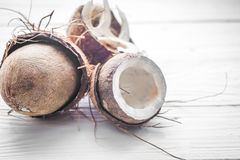 halves of coconut on a white wooden background Stock Photography