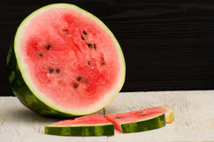 Halves cut watermelon slices on a light wooden table, black background Stock Images