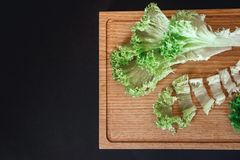 Halves of fresh cabbage on old brown wooden table on black background with copy space. Top view royalty free stock photo