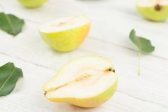 Halves of fresh ripe yellow pears and green leaves royalty free stock photography