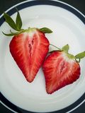Halves of fresh strawberry in the shape of a heart. On a plate stock photos