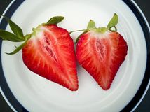 Halves of fresh strawberry in the shape of a heart. On a plate royalty free stock images