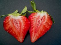 Halves of fresh strawberry in the shape of a heart. On dark background stock photos