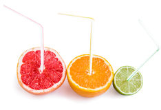 Halves of grapefruit, orange and lime with straws on white. Royalty Free Stock Photo