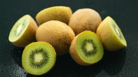 Halves of green kiwi. Closeup of pile of whole and halves of kiwi with green flesh composed on wet glass surface with water drops royalty free stock photography