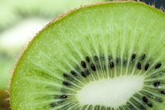 Halves of kiwi fruit. A green heart and halves of kiwi fruit with seeds, closeup stock photos